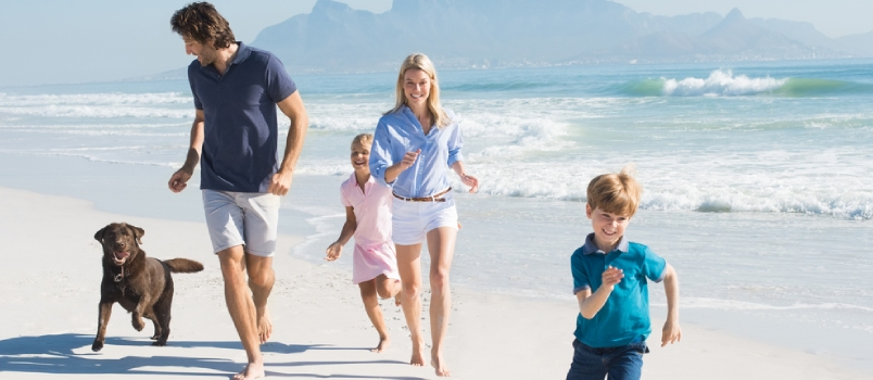 Family Playing With Pet On The Beach. Happy Beautiful Family Running At Beach With Pet Dog