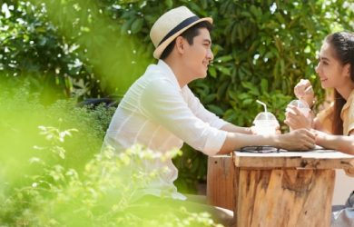 Side View Of Young Couple Sitting In Outdoors Cafe When Having Date