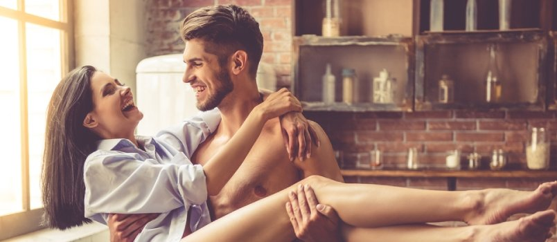 Sexy Young Man With Bare Torso Is Holding His Beautiful Girlfriend In Arms While Standing In Kitchen At Home & Both Are Looking At Each Other And Smiling
