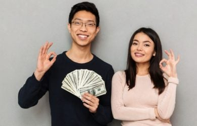 Young Asian Loving Couple Standing Isolated Over Grey Wall Background Holding Money Showing Okay Gesture