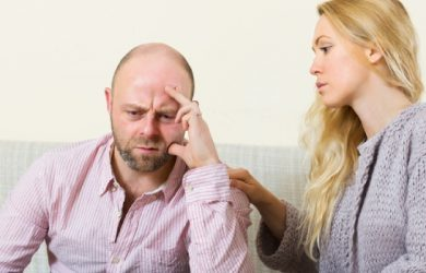 Sad Man Has Problem, Woman Consoling Him On Sofa At Home
