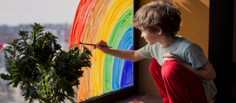 Child At Home Draws A Rainbow On The Window