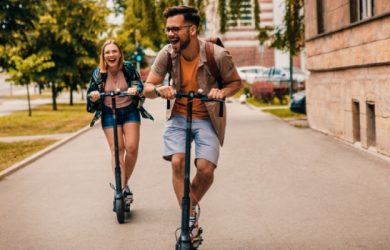 Young Couple On Vacation Having Fun Driving Electric Scooter Through The City