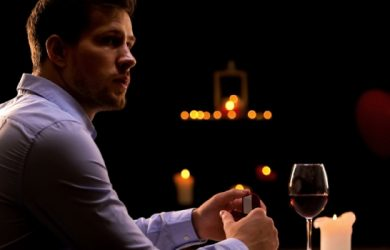 Man With Engagement Ring Sitting Alone In Restaurant