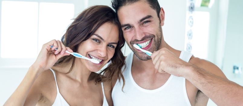 Portrait Of Happy Couple Brushing Teeth In Bathroom At Home