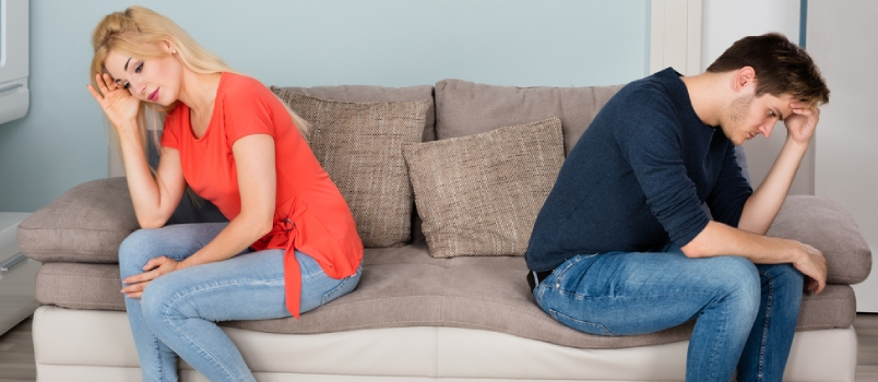 Sad Angry Divorcing Couple Sitting Back To Back On Sofa At Home