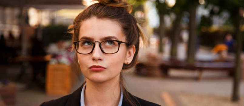 Portrait Of Young Woman In Glasses Is Pondering Outdoor.