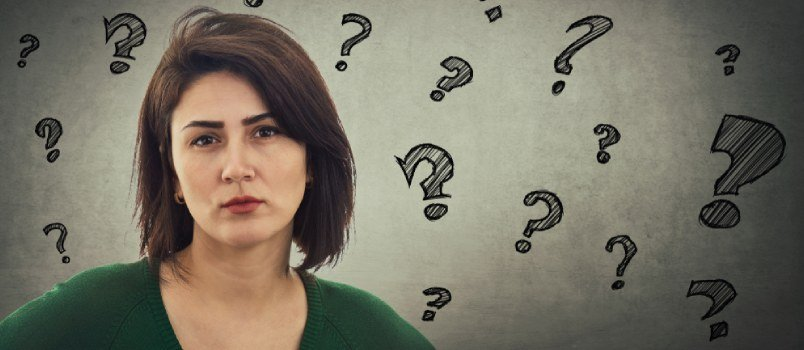 Upset Women Looking Sadly With Multiple Question Mark Background On The Wall