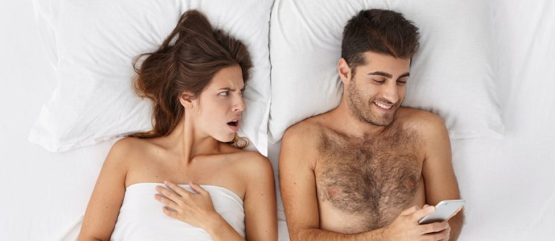 Men And Women Lying Together On Bed, Men Using Cellphone While Irritated Women Staring At Husband
