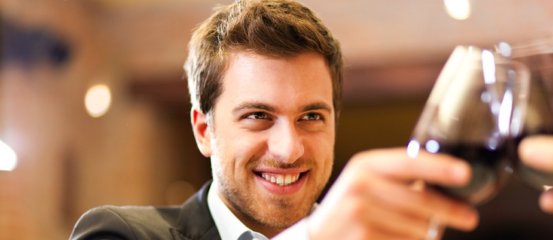Young Handsome Guy With Glass Of Wine In Party Cheers