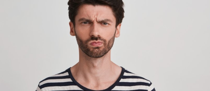 Clouse Up Of Young Brown Hair Man With Beard Looks Displeased, Eyebrows Furrowed, His Mouth Twisted In One Side Wears Black And White Striped Tshirt,