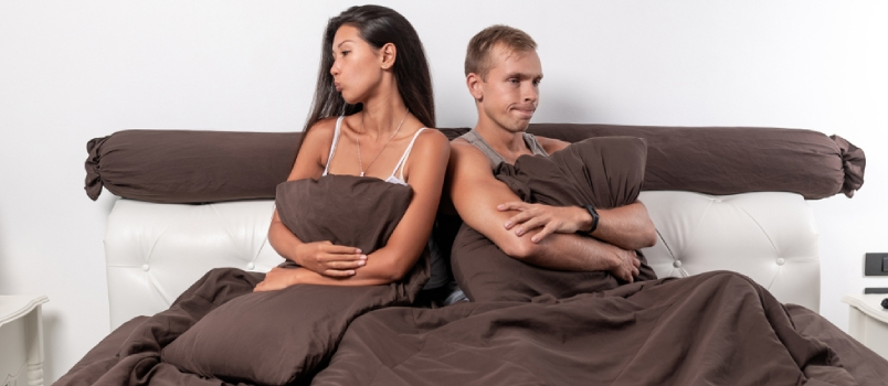 A Young Couple Of Lovers Sits In Bed With Arms Crossed On Their Chest, Turning Away From Each Other