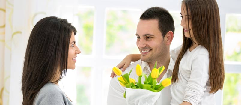 Husband And Daughter Giving Her Women A Flowers Bookey On Mothers Day Occasion