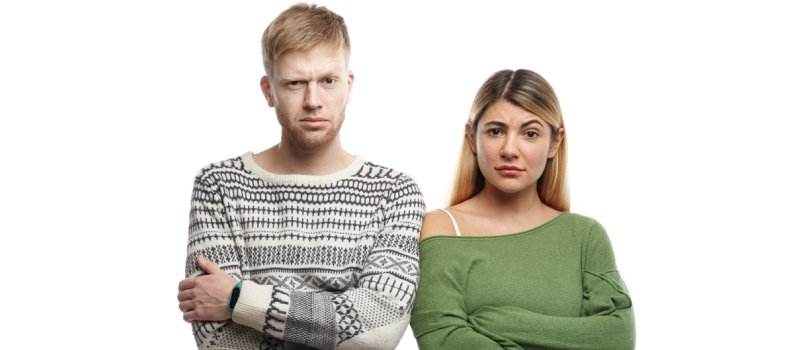 Horizontal Shot Of Distrustful Young Couple Crossing Arms In Studio And Staring At Camera, Having Doubtful Skeptical Looks