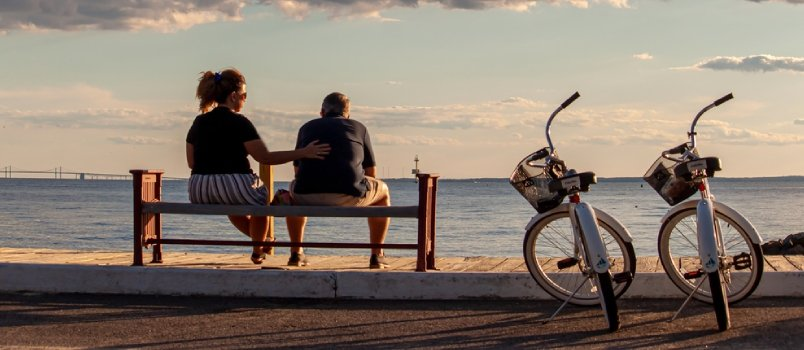 A Middle Aged Caucasian Couple Is Sitting On A Bench By The Beach. They Have Their Identical Bikes Parked Next To Them