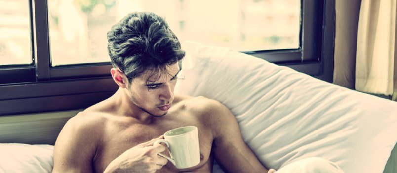 Young Shirtless Handsome Guy Having Coffee In The Morning On His Bed