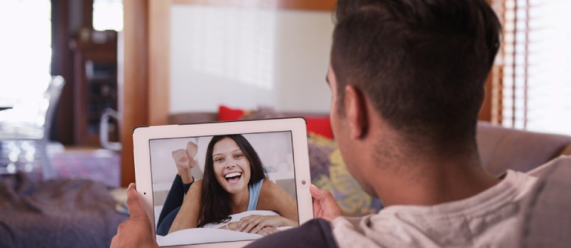 Back Camera View Man Video Chatting On Tablet With A Woman She Looks Very Excited
