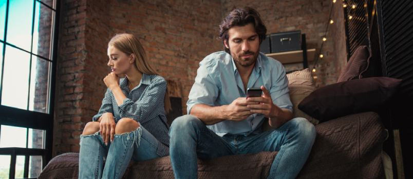Off Husband And Wife Sitting On Couch At Living Room And While Man Using Cellphone