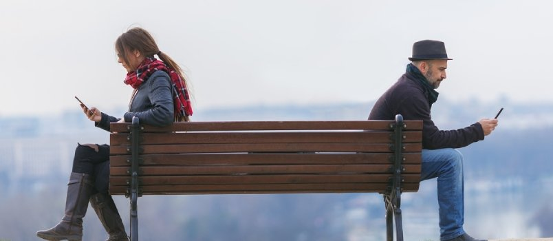 Man And Woman Sitting Apart On A Park Bench And Using Mobile