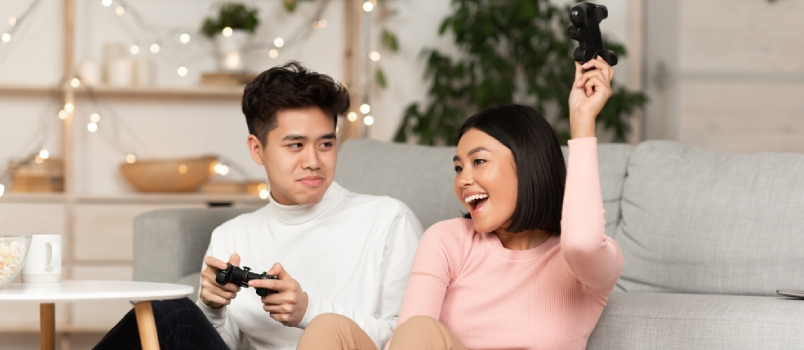 Korean Young Couple Playing Video Games Together, Asian Husband Losing Videogame To Wife Sitting In Living Room At Home