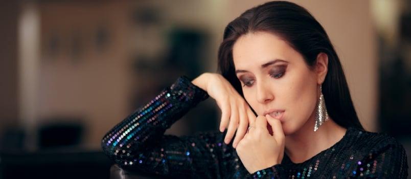 Sad Bored Glamorous Woman Having No Fun At Party Sitting Alone And Biting Her Nails