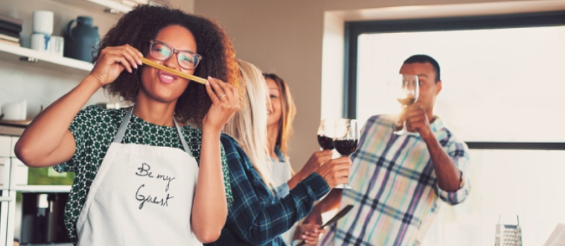 Funny African Girl In Glasses Making Face With Fake Moustache Made Of Spaghetti With Her Friends Cheering On Background With Wine Glasses.
