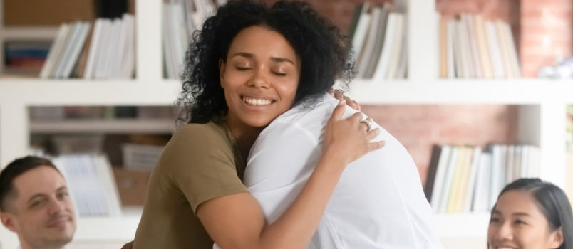 Relieved Smiling Black Woman Hug With Friend Showing Support And Empathy At Group Therapy Session