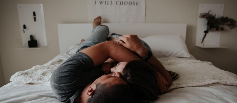 Young Attractive Couple Lying Together On Bed Having Romance At Bedroom