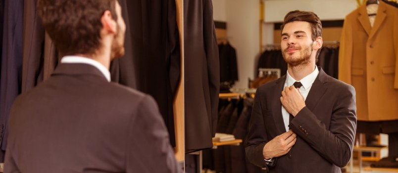 Modern Young Handsome Businessman Dressed In Classical Suit Adjusting A Tie In Front Of The Mirror While Standing In The Suit Shop