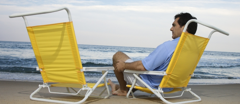 Man sits on the beach alone and looks at an empty chair. Horizontal shot