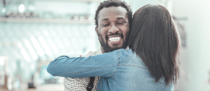 Joyful Positive Nice Man Smiling And Hugging His Friend While Meeting