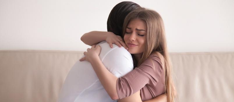 Retrato de jovem casal emocional se abraçando fortemente, namorado e namorada se abraçando sentados no sofá