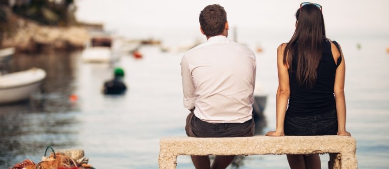 Romantic Couple On A Date In Nature, Sitting On The Bench Looking At Serene Ocean Scene