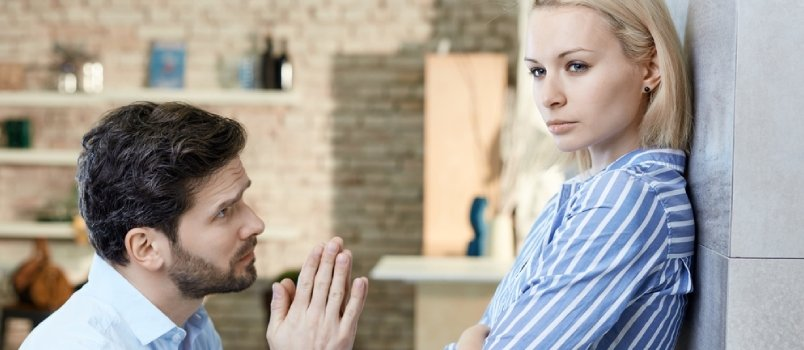 Young Man Asking Sulky Girlfriend's Forgivenes At Home On Bended Knees