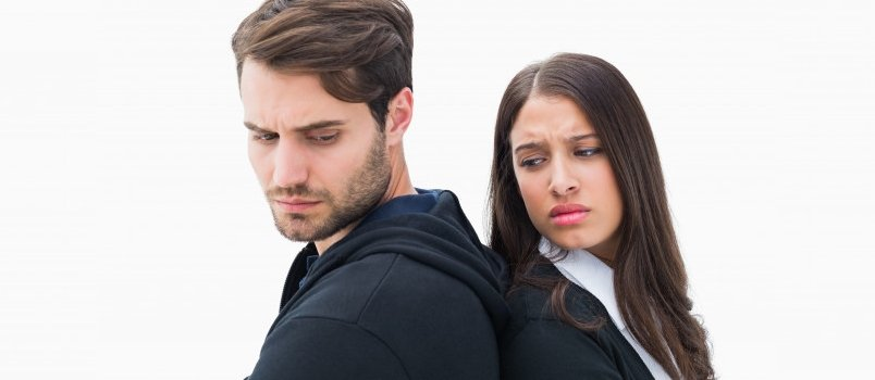 Unhappy Couple Standing With White Isolated Background Wall And Looking Crossed Eyes To Each Other