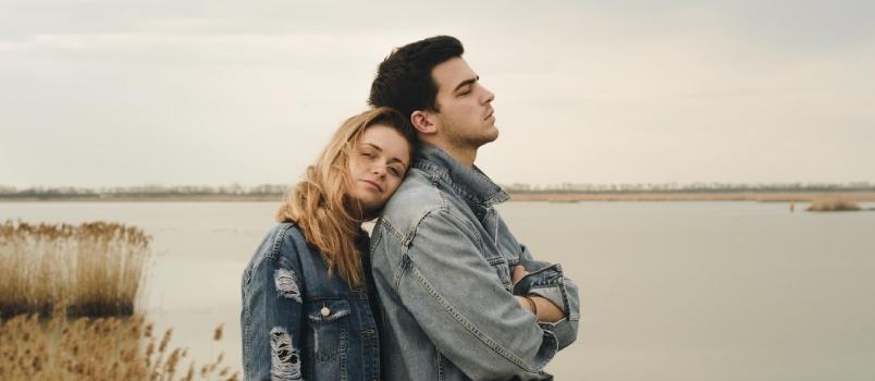 Woman In Blue Denim Jacket Leaning On Man's Shoulder In Love Near Body Of Water