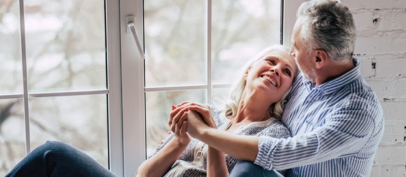 Handsome Old Man And Attractive Old Woman Are Hugging And Enjoying Spending Time Together While Sitting On A Window Sill