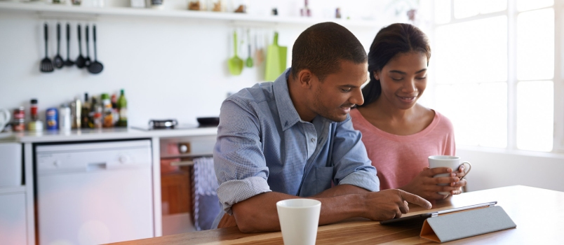 Asian Man And Women Watching Somthing On Tablet At Kitchen