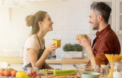 Happy Loving Couple Chatting During Coffee Break Standing At Home Kitchen