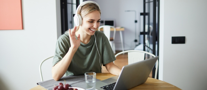 Cheerful Girl In Headphones Waving Her Hand To Friend While Communicating Through Video-chat In Front Of Laptop