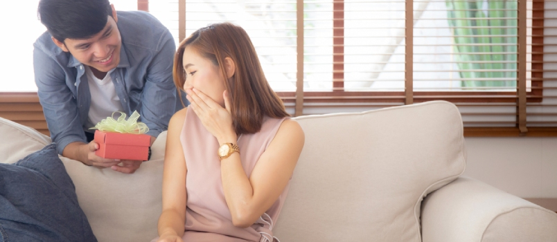 Asia Man Giving Gift Box Present To Woman For Surprise At Living Room