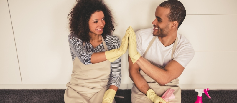 Beautiful Young Afro American Couple Is Giving High Five And Smiling While Sitting On The Floor In Kitchen After Cleaning It