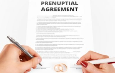 Man And Woman Sign Prenuptial Agreement Near Gold Rings