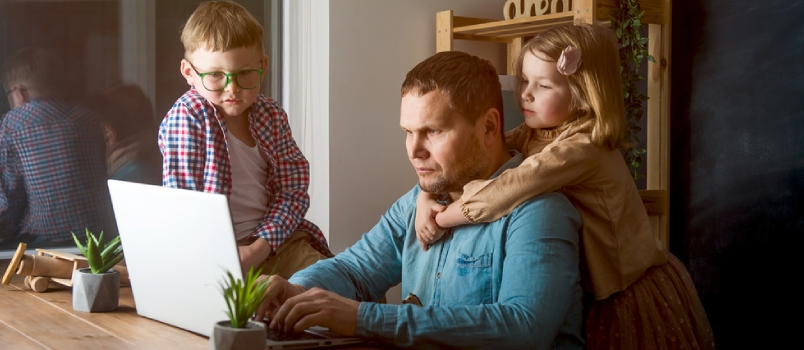 Man Works On Laptop With Children Playing Around Family Together