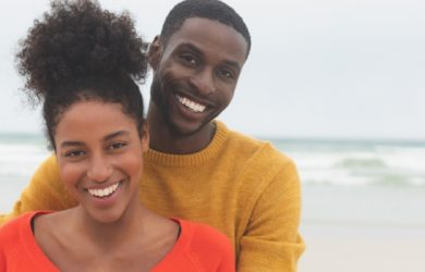 Portrait Of Diverse Couple Standing At Beach They Are Smiling And Looking At Camera