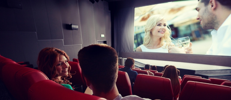 Happy Couple Of Friends Watching Movie And Talking In Theater From Back