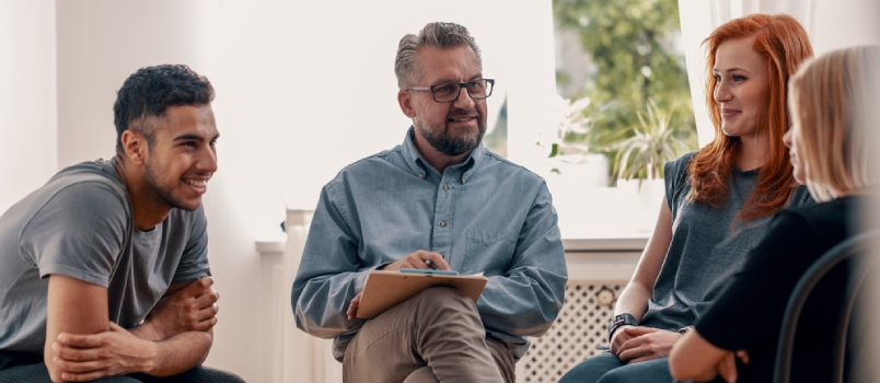 Smiling Spanish Man Talking To His Friends During Meeting For Teenagers With Therapist