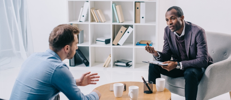 African American Psychiatrist Talking To Young Male Client At His Office With Coffee