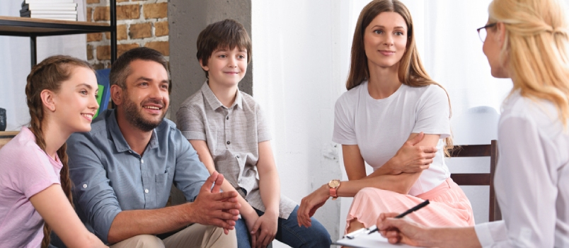 Happy Family Sitting On Therapy Session By Female Counselor