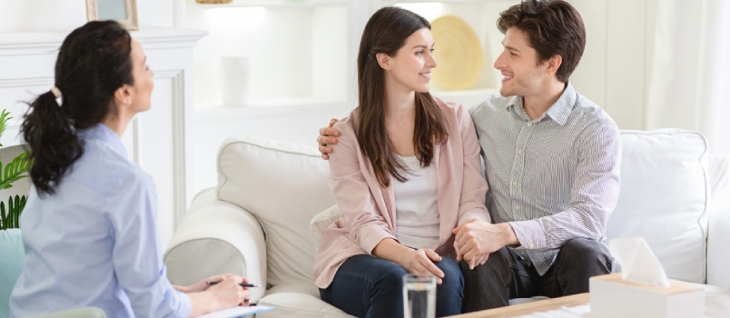 Happy Couple At Therapy Session With Family Psychologist Smiling And Look At Each Other